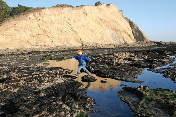 Child jumping over tidepool